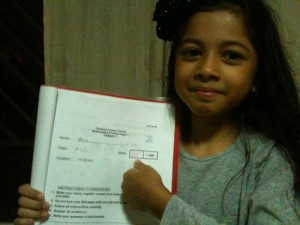 Amira proudly showing her full marks for Maths